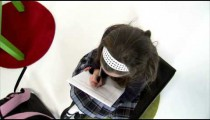 Royalty Free Stock Footage of Move above a girl doing homework on white.