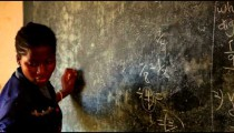Close up of teacher erasing a chalkboard in Kenya.