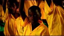Close up of a boy raising his hand at school in Kenya.