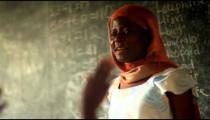 African Schoolteacher in a full classroom in Kenya.
