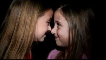 Royalty Free Stock Footage of Young twin girls touching noses.