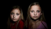 Royalty Free Stock Footage of Young twin girls staring at the camera.