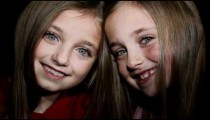 Royalty Free Stock Footage of Young twin girls smiling at each other.