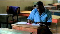 School boy doing homework in an empty classroom in a school in Kenya.
