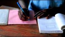Close up of hands of a school boy doing homework in Kenya.