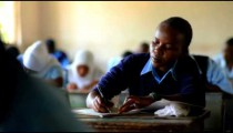 Students taking a test in a school in Africa.