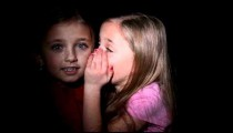 Royalty Free Stock Footage of Young twin girls whispering to each other.