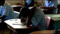 Students taking a test in a schoolroom in Africa.
