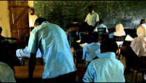 Students taking a test in a classroom in Africa.