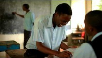 Students taking a test in a class in an African school.