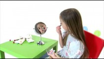 Royalty Free Stock Footage of Young girl putting blush on her cheeks.