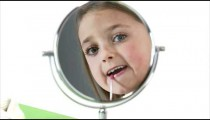 Royalty Free Stock Footage of Young girl putting on lip gloss.