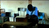Students taking an exam in class in a school in a village in Kenya.