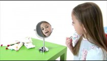 Royalty Free Stock Footage of Young girl putting lip gloss on her lips.