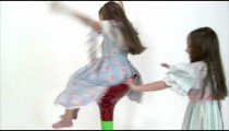 Royalty Free Stock Footage of Young twin girls playing on a tall chair on a white background.
