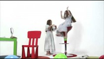 Royalty Free Stock Footage of Young girl being spun on a chair by her twin.
