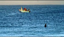 Stock Video Footage of a surfer and fishing boat on the Mediterranean shot in Israel at 4k with Red.