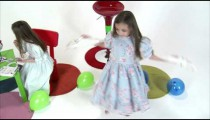 Royalty Free Stock Footage of Young twins, one spinning, one applying makeup.