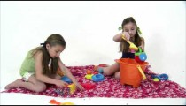 Royalty Free Stock Footage of Young twin girls on a pretend beach playing.