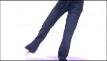 Tilt down shot of a girl dancing in a purple shirt.