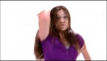Tilt down shot of a girl in a purple shirt dancing.