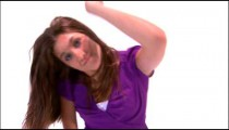 Dancing girl in a purple shirt and jeans.