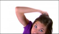 Clip of a girl dancing in a purple shirt and jeans.