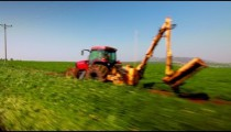 Stock Footage drive-by of a tractor and a green field in Israel.