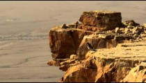 A bird hopping on a cliff edge shot in Israel.