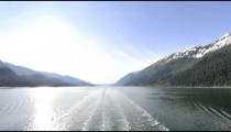 Traveling time lapse view of the Inside Passage from behind a cruise ship in Alaska
