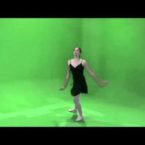 Clip of a ballerina in black dancing on a green screen.