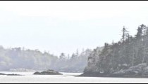 Traveling time lapse view of the Inside Passage with a foggy mist over the landscape in Alaska