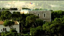 Panning shot of Jerusalem trees and flags in the wind filmed in Israel.