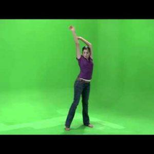 Shot of a girl in a purple shirt dancing on a green screen.