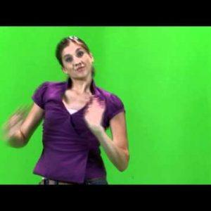 Shot of a girl dancing on a green screen in a purple shirt.