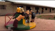 African kids playing on merry go round.