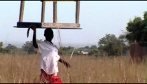 Royalty Free Stock Footage of African woman carrying a table on her head.