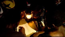 Royalty Free Stock Footage of African children reading around a lamp.