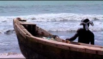 Man and a boat on shore in Africa.