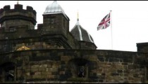 United Kingdom flag waving above an old fortress in England.