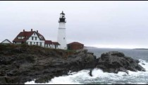 Portland Head Light with waves on the rocky shore in Maine.