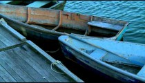 Two old wooden rowboats tied to a dock.