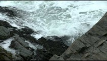 Close-up of waves crashing on a rocky shore in Maine.