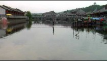 Man tight-rope walking over a river in China.