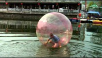 Man in a plastic ball on a river in China.