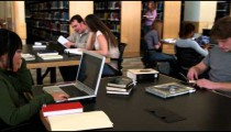 Clip of students in a library studying.
