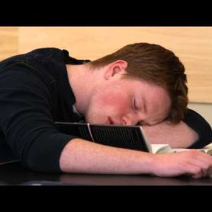 Close-up of a student sleeping while reading.