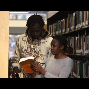 Dolly shot of people in-between bookshelves at a library.