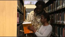 Clip of people in-between bookshelves at a libraray.