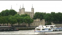 Tower of London with boats passing in the foreground.